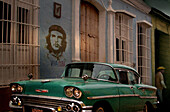 Street scene with oldtimer and Che Guevara wall painting, Trinidad, Sancti Spiritus, Cuba, Carribean, North America, America