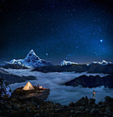 Night sky over snowcapped mountains, Man camping near prayer flags, Pokhara, Kaski, Macchapucchare, Annapurna, Nepal, Asia