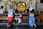 Women and child kneeling and praying, Cebu Metropolitan Cathedral, Philippines, Asia