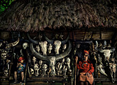 Old woman and boy in front of a hut with straw roof and buffalo skulls, Ifugao, Luzon, Philippines, Asia