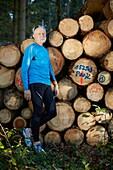 Älterer Mann an einem Holzstoss im Wald, Laufen, Joggen, Sport