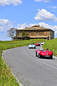 Red Maserati Oldtimer on a road near a house through the Tuscan valley, Mille Miglia, 1000 Miglia, 2014, San Quirico D´orcia, Siena, Tuscany, Italy, Europe