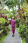 Balinese worker walking along path, Ubud, Bali, Indonesia
