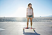 African American woman riding longboard on beach, Los Angeles, California, USA