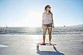 African American woman riding longboard on beach, Los Angeles, California, USA
