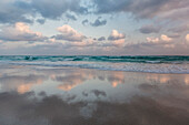 Clouds and sky reflected in still beach surf at sunrise, Qalansyia, Socotra, Yemen