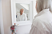 Senior Caucasian woman admiring herself in mirror, Toronto, Ontario, Canada