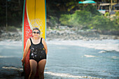 Older Hispanic woman with surfboard on beach, Sayulita, Nayarit, Mexico