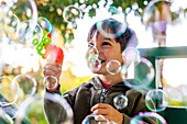 Mixed race boy playing with bubbles outdoors, Oakland, California, United States