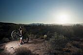 Mountain biker standing in desert, Fountain Hills, Arizona, USA