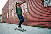 Mixed race woman riding skateboard on city street, Los Angeles, California, USA