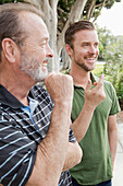 Older Caucasian man relaxing with son outdoors, Los Angeles, CA, USA