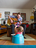 Caucasian father playing guitar for daughter, Los Angeles, California, USA