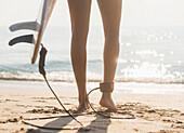 Woman tethered to surfboard on beach, Jupiter, Florida, USA