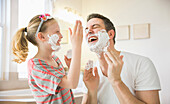 Caucasian father and daughter playing with shaving cream, Lehi, Utah, USA