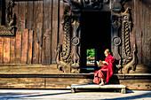Asian monk reading by ornate doorway to temple, Mandalay, Mandalay, Myanmar
