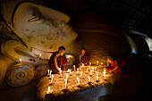Asian monks lighting candles in temple, Bagan, Mandalay, Myanmar
