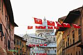 Flags flying over city street, Pisa, Toscano, Italy, , Pisa, Toscano, Italy