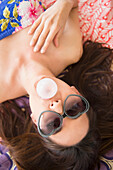 Woman in sunglasses blowing bubble gum bubble on rug, Jersey City, New Jersey, USA