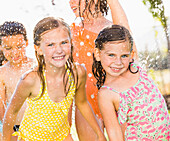 Caucasian children playing in sprinkler in backyard, Lehi, Utah, USA