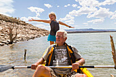 Older Caucasian man rowing kayak with granddaughter, Abiqui, New Mexico, USA
