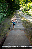 Caucasian boy climbing stairs near rural path, C1