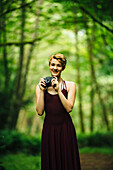 Caucasian woman holding camera in forest, C1