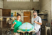 Father and son gesturing hang ten in surfboard workshop, C1