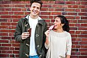 Caucasian couple eating ice cream near red brick wall, Seattle, Washington, United States