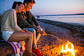 Caucasian couple roasting marshmallows on fire at beach, Seattle, Washington, United States