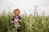 Caucasian boy standing in tall grass in rural field, Ekaterinburg, Ural, Russia