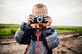 Caucasian boy taking photograph in rural field, Ekaterinburg, Ural, Russia