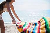 Caucasian woman spreading blanket on beach, Jupiter, Florida, USA