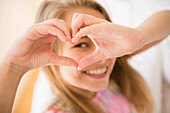 Caucasian girl making heart shape with hands, Jersey City, New Jersey, USA