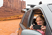 Caucasian girl taking cell phone photograph from car, Monument Valley, Utah, United States, Monument Valley, Utah, USA
