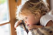 Caucasian baby boy peering over back of sofa in living room, Santa Fe, New Mexico, USA