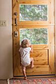 Caucasian baby boy peering out door window, Santa Fe, New Mexico, USA
