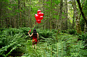 Korean woman holding red balloons in lush forest, Bainbridge Island, WA, United States