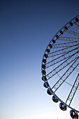 Low angle view of ferris wheel against blue sky, Seattle, Washington, United States