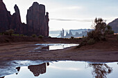 Rock formations overlooking puddles in desert landscape, Monument Valley, Utah, United States, Monument Valley, Utah, USA