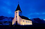 White church illuminated near snowy mountains at night, Vik, Sudhurland, iceland