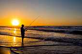 Silhouette of man fishing in waves on beach at sunset, Coast, New York, USA