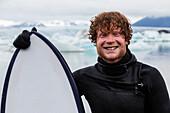 Caucasian surfer holding board near glacial water, Jokulsarlon, Iceland, Iceland