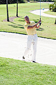 Caucasian man golfing from sand trap on golf course, Palm Beach, Florida, USA