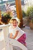 Caucasian baby boy climbing adirondack chair on patio, Santa Fe, New Mexico, USA