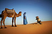 Tourist photographing guide with camel on sand dune in desert landscape, Sahara Desert, Morocco, Morocco