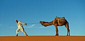 Guide pulling camel on sand dune, Sahara Desert, Morocco, Morocco