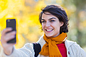Mixed race woman taking cell phone selfie outdoors, Santa Fe, New Mexico, USA