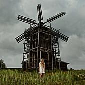 Caucasian teenage girl standing under wooden windmill, Nizniy Tagil, Sverdlovsk, Russia