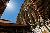 Low angle view of carved Buddha statue in rock wall, Mulbekh, Kashmir, India